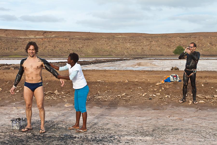 Два белых мужчины в целебной грязи в плавках. Соляное озеро в жерле вулкана. Педра-де-Люме, остров Сал, Кабо-Верде. Two white men applying  healing mud in speedo swimming trunks. Salina, Salt lake, Pedra de Lume, Sal island, Cape Verde