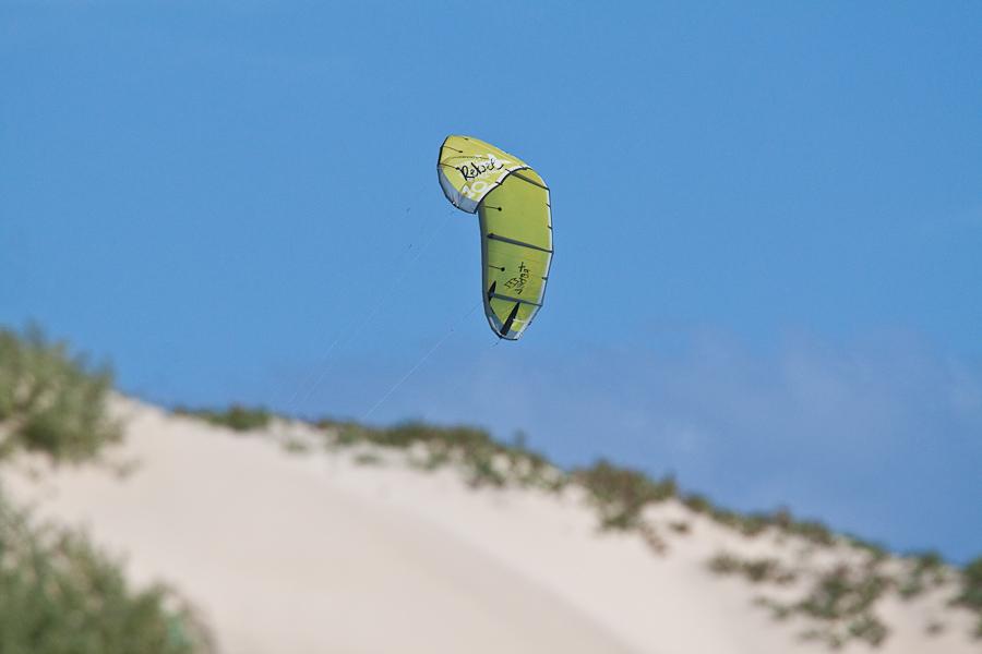 Кайт-сёрферский парус выглядывает из-за песчасной дюны, остров Сал, Кабо-Верде. A Kite Surfing sail seen from a sandy dune, Sal island, Cape Verde