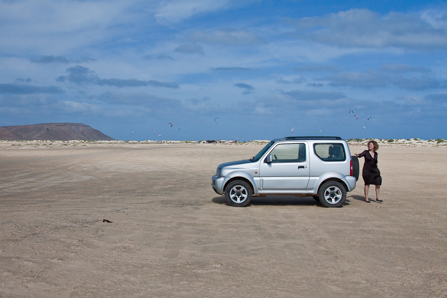 Девушка и джип на фоне кайт-сёрферов и гор. Пустынный песчасный остров Сал, Кабо-Верде. A lady with Suzuki Jimny with a mountain and kite surfers in the background. Sal island, Cape Verde