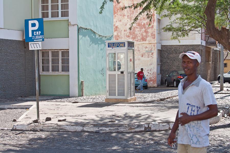 Мужчина, телефонная будка и знак парковки на улице города Прая. Кабо-Верде, остров Сантьягу.