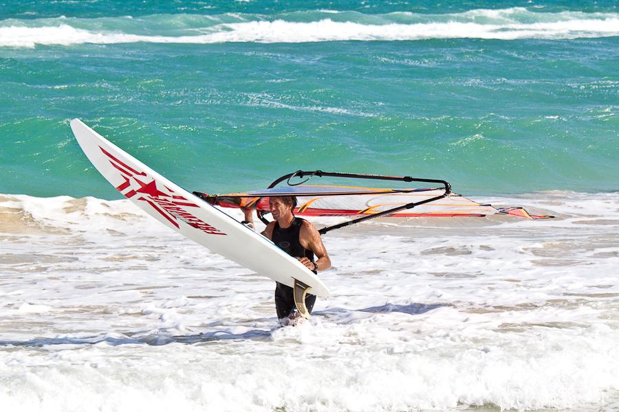 Виндсёфер несёт доску с парусом. Песчасный пляж и океанский прибой. Остров Сал, Кабо-Верде. Windsurfer. Sandy beach and ocean waves, Sal island, Cape Verde