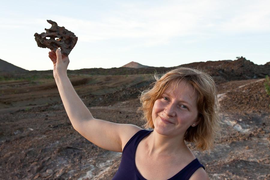 Женщина/девушка держит дырявый/пористый камень вулканической пемзы. Остров Вознесения, Атлантический океан. A woman holds a holey rock of volcanic pumice, Ascension island, South Atlantic
