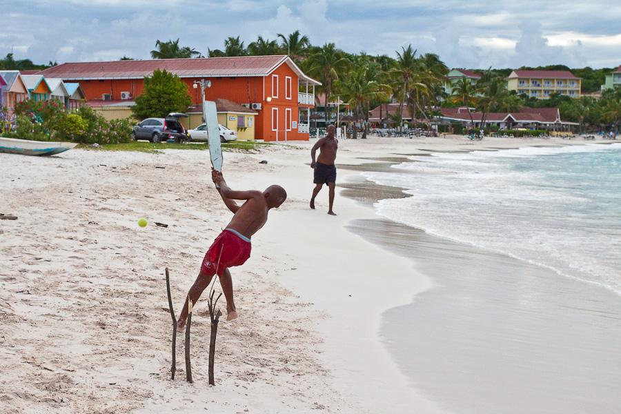 Father and son are playing cricket on Long Bay beach, Antigua, Antigua and Barbuda, Leeward Islands, West Indies, Caribbean. Чёрный отец и чёрный сын. Игра в крикет на пляже Лонг-бэй, остров Антигуа, Антигуа и Барбуда, Карибы.