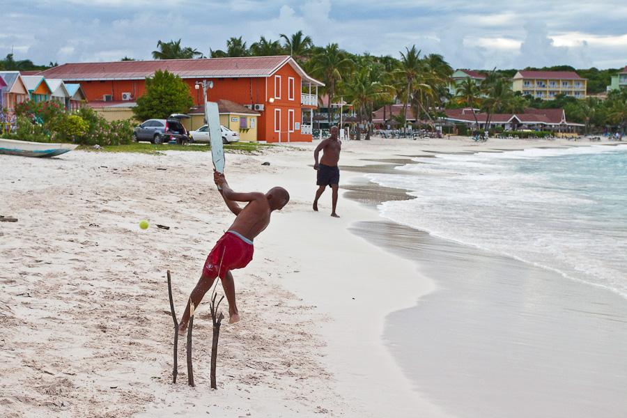 Father and son are playing cricket on Long Bay beach, Antigua, Antigua and Barbuda, Leeward Islands, West Indies, Caribbean. Чёрный отец и чёрный сын. Игра в крикет на пляже Лонг-бэй, остров Антигуа, Антигуа и Барбуда, Карибы.