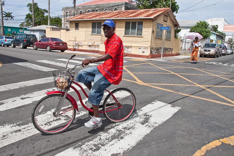 Black man riding a bicycle on Street of St. John's city, Antigua island, Antigua and Barbuda, Caribbean. Чёрный велосипедист на улице города Сент-Джонс, остров Антигуа, Антигуа и Барбуда, Карибский бассейн.