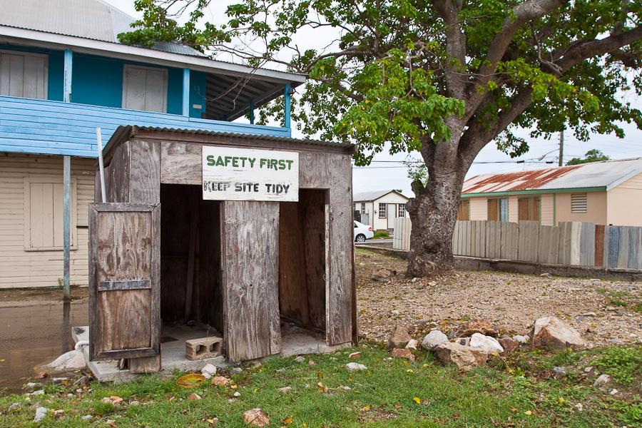 Old loo outdoor wooden rustic toilet, St. John's city, Antigua island, Antigua and Barbuda, Caribbean. Safety First, Keep site tidy sign. Старый деревянный туалет на два очка, город Сент-Джонс, остров Антигуа, Антигуа и Барбуда, Карибский бассейн.