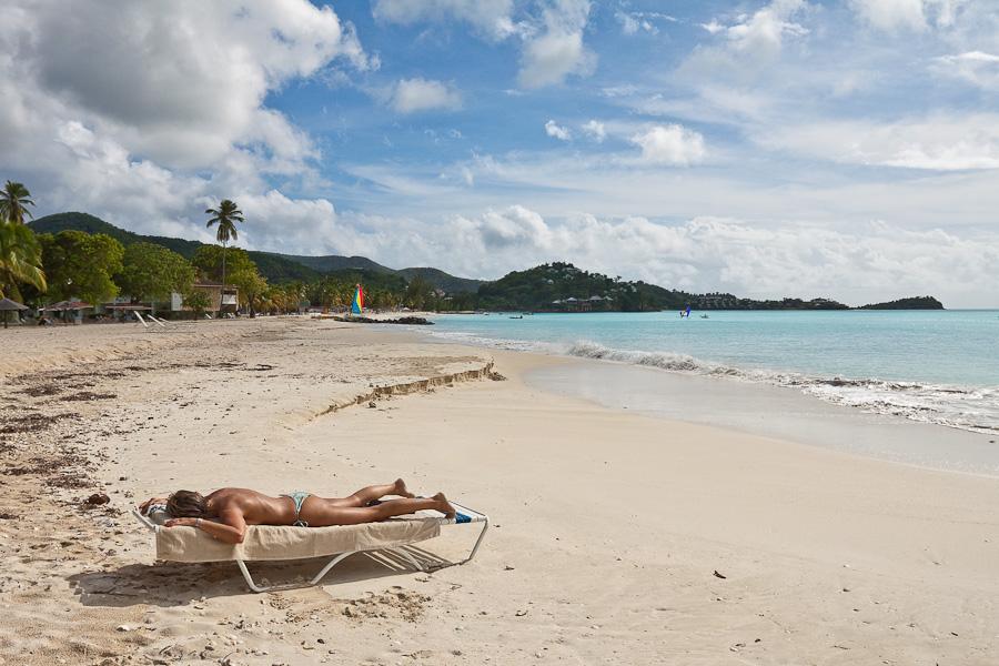 Half-naked topless lady on a beach sunbathing, Antigua, Antigua and Barbuda, Leeward Islands, West Indies, Caribbean. Пляж, женщина загарает без верха топлесс, остров Антигуа, Антигуа и Барбуда, Карибы.
