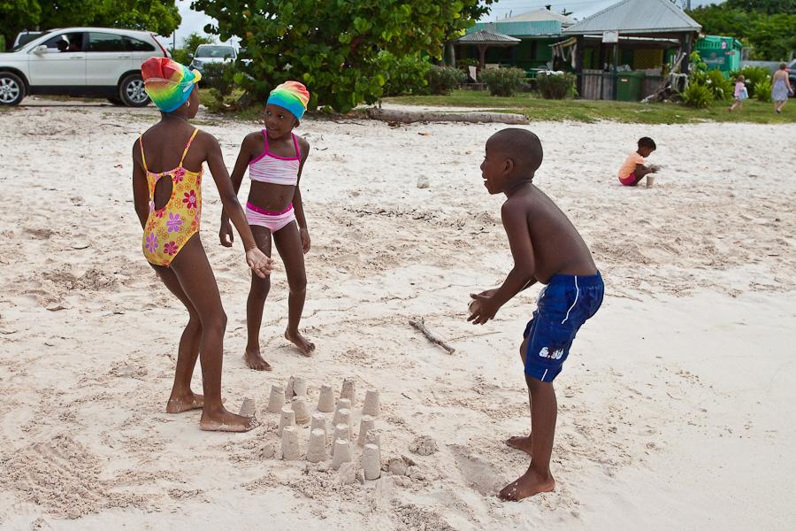 Black kids are playing in sand on Long Bay beach, Antigua, Antigua and Barbuda, Leeward Islands, West Indies, Caribbean. Две чёрные девочки готовятся уничтожить куличики чёрного мальчика, негритята, игра в песок на пляже Лонг-бэй, остров Антигуа, Антигуа и Барбуда, Карибы.