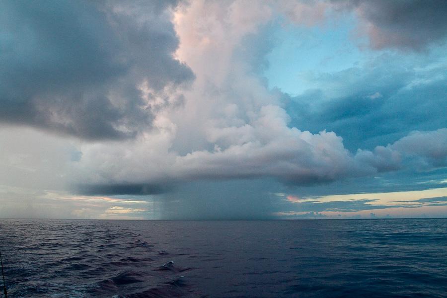 Туча и дождь в Тихом океане между Гамбье и Питкэрном
