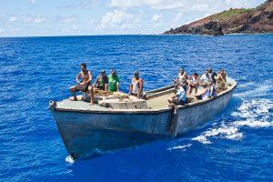 Фото. Жители острова Питкэрн встречают гостей острова на баркасе (longboat)