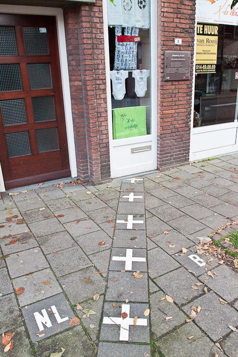 Граница на тротуаре. Госграница делит улицу и дом между странами в бельгийском городе Барле-Хертог и голландском Барле-Нассау. Border divides a street and a house between countries in Belgian town Baarle-Hertog and Dutch town Baarle-Nassau