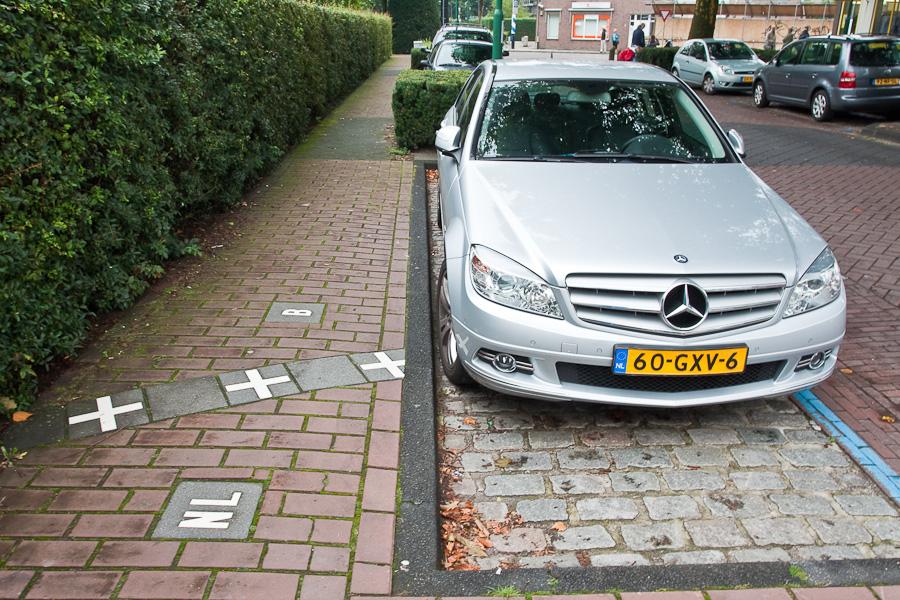 Граница на тротуаре. Мерседес. Госграница делит тротуар и парковку между странами в бельгийском городе Барле-Хертог и голландском Барле-Нассау. Border divides a street between countries in Belgian town Baarle-Hertog and Dutch town Baarle-Nassau. Mercedes-Benz