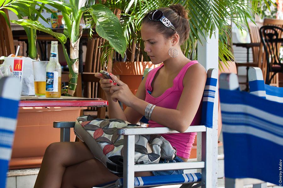 Papeete streets, Tahiti, French Polynesia. French polynesian girl texts in a cafe. Улица города Папеэте, Таити, Французская Полинезия. Французская полинезийская девушка сидит в кафе, пишет смс