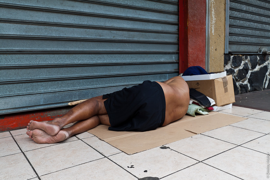 A man sleeping on street of Papeete, Tahiti, French Polynesia. Мужчина спит на улице в городе Папеэте, Таити, Французская Полинезия.