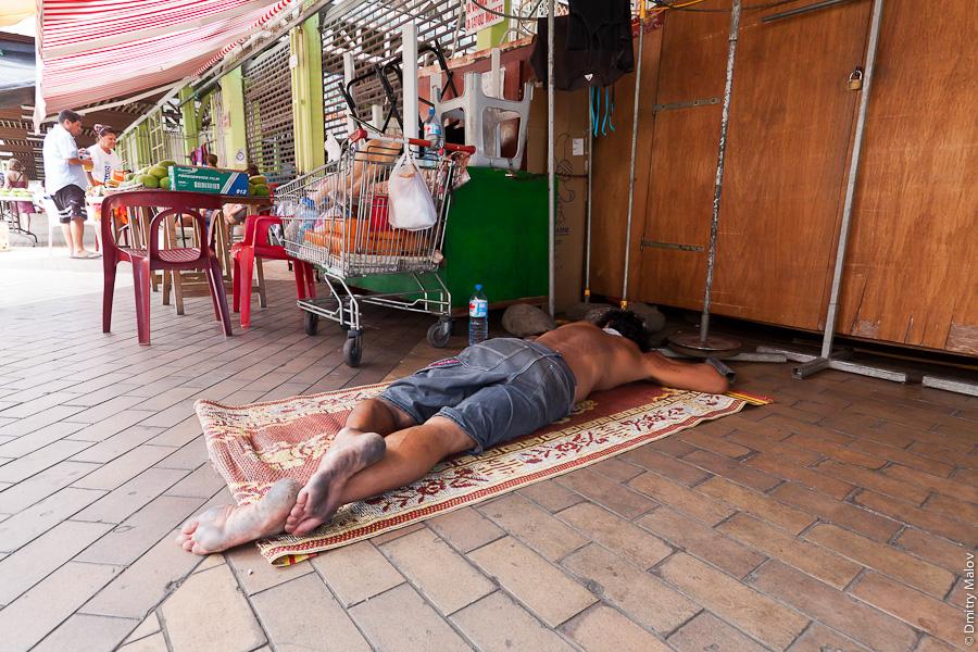A man sleeping on street, Marché de Papeete, Market, Papeete, Tahiti, French Polynesia. Мужчина спит на улице, на рынке в городе Папеэте, Таити, Французская Полинезия.