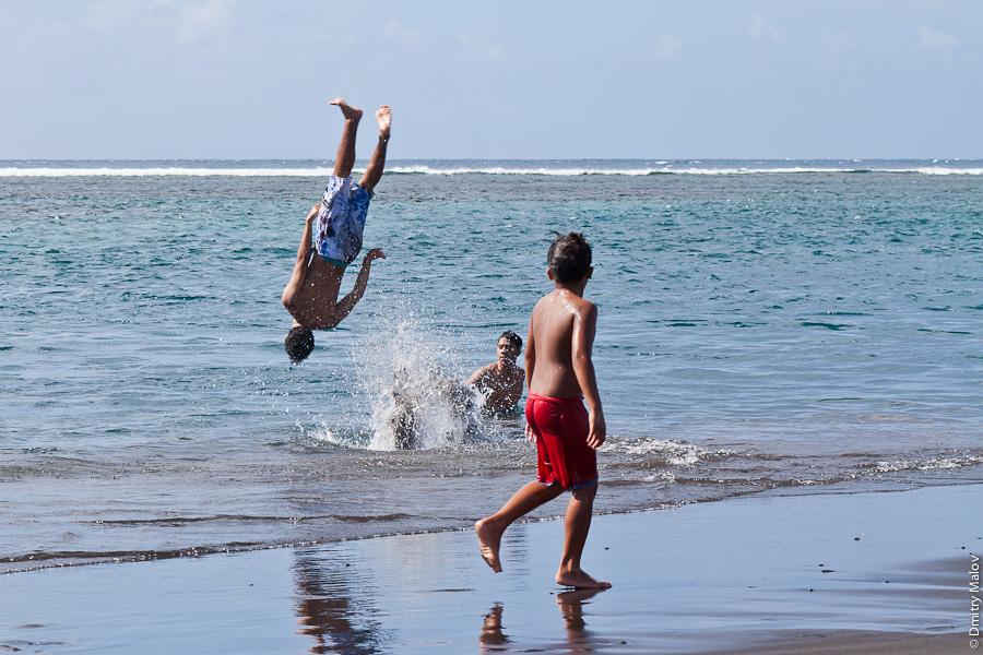 Venus beach, Pointe Venus, Tahiti, French Polynesia. Ocean, black sand, boys/guys/kids playing/jumping/swimming. Пляж Пойнте-Венус, Таити, Французская полинезия, пляж с чёрным песком, парни/мальчики/дети играют/прыгают/купаются