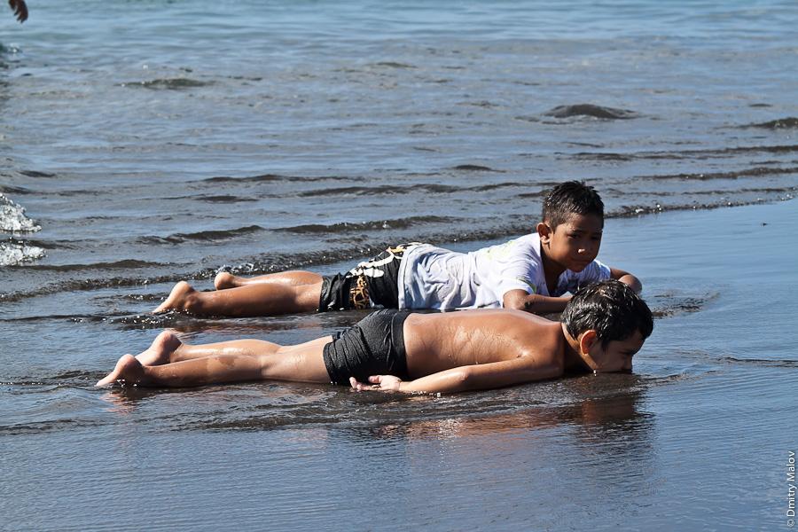 Venus beach, Pointe Venus, Tahiti, French Polynesia. Ocean, black sand, boys/guys/kids lying on beach/swimming/boy eating sand. Пляж Пойнте-Венус, Таити, Французская полинезия, пляж с чёрным песком, парни/мальчики/дети лежат на песке/купаются/едят песок