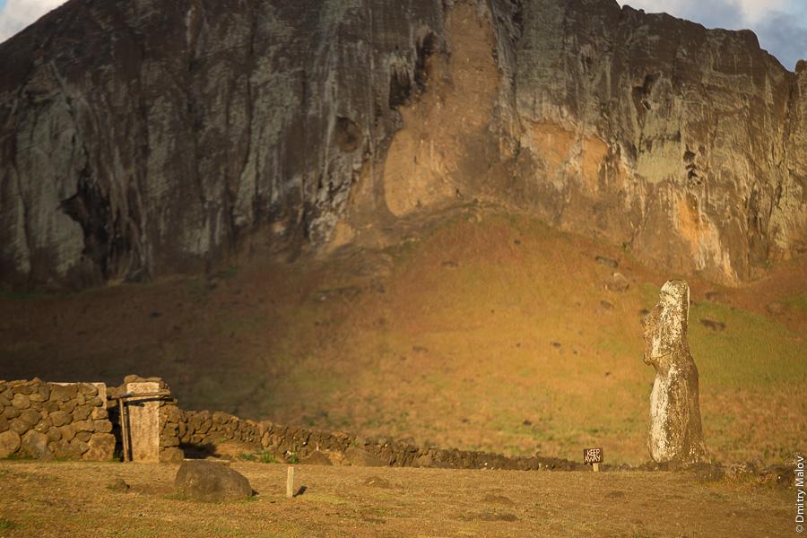 Вид на статую моаи (тики) около Аху Тонгарики на фоне вулкана Рано Рараку, остров Пасхи (Рапа-Нуи). View of a Tiki (Moai) statue near Ahu Tongariki with Rano Raraku volcano in the background, Easter Island (Rapa Nui)