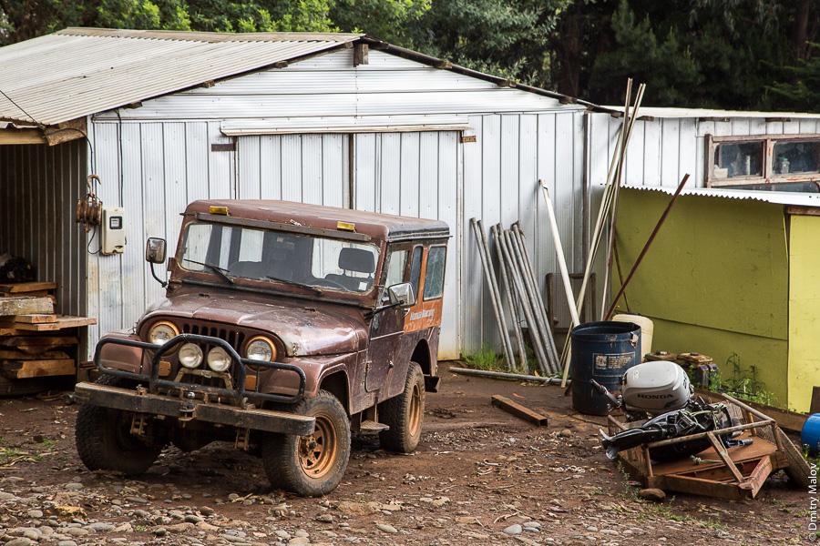 Джип на улице города Сан-Хуан-Батиста, остров Робинзона Крузо, архипелаг Хуан-Фернандес, Чили. A Jeep 4x4 on a San Juan Bautista town street, Robinson Crusoe Island (Más a Tierra), Juan Fernández Islands, Chile