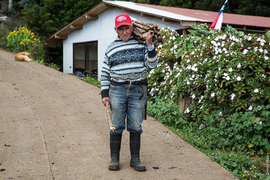 Местный житель несёт дрова, улица города Сан-Хуан-Батиста, остров Робинзона Крузо, архипелаг Хуан-Фернандес, Чили. A local carrying firewood, San Juan Bautista town streets, Robinson Crusoe Island (Más a Tierra), Juan Fernández Islands, Chile
