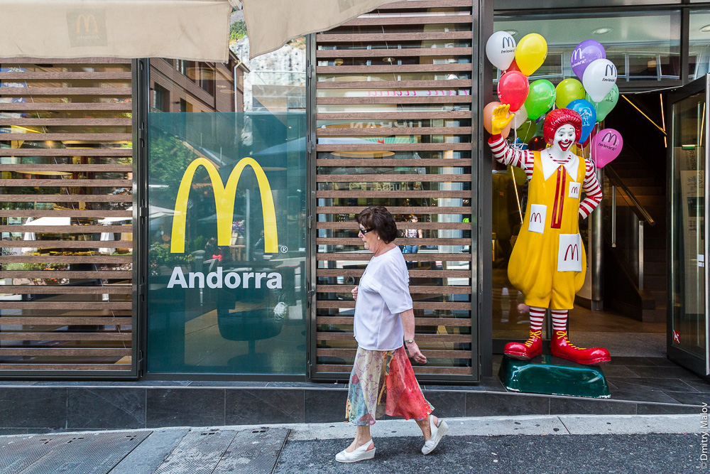 Woman walking on a street of Andorra la Vella by McDonalds restaurant. Женщина идёт по улице Андорра-ла-Велья мимо ресторана МакДональдс