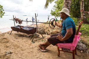 Фото с Тонги. Полинезиец жарит свинью на берегу океана