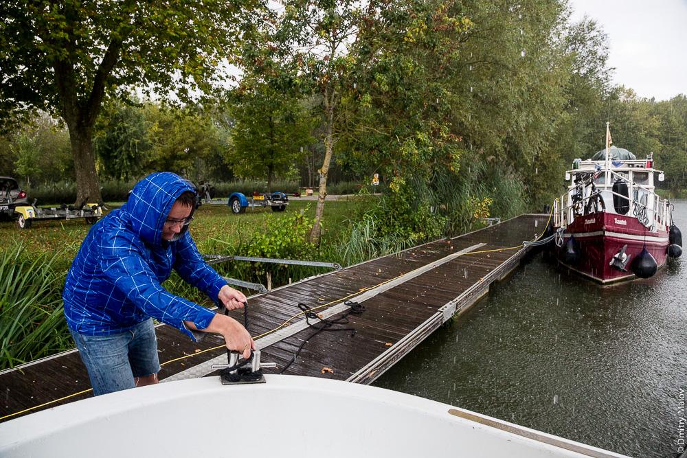 Дмитрий Малов привязывает морским узлом/швартует пенишет в Кюизери, Франция. Вечереет. Холодно, дождь, противно, швартовка