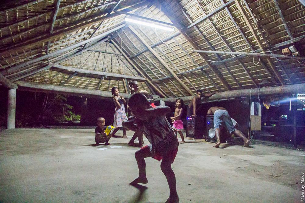 Взрослые местные микронезийцы и дети танцуют ночью внутри в традиционном общественном доме — манеаба. Музыкальный центр, колонки. People and kids are dancing inside a maneaba (traditional meeting house) in the evening. Music center and speakers. Атолл Тарава, Кирибати, Микронезия. Tarawa atoll, Kiribati, Micronesia.
