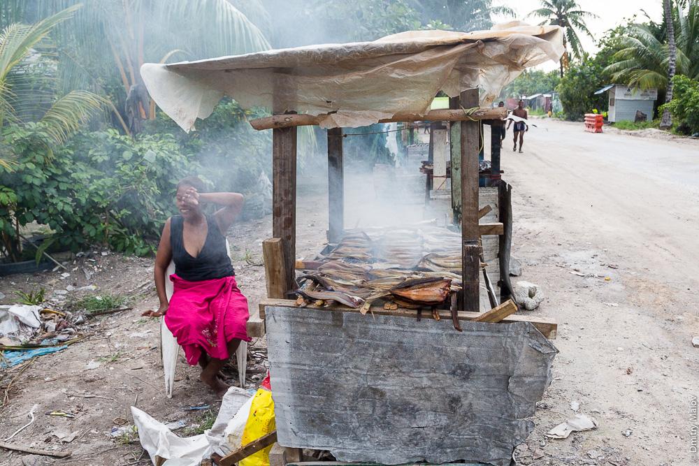Местная жительница коптит и продаёт рыбу. Южная Тарава, Кирибати, Микронезия. Local woman selling smoked fish from a food stall. South Tarawa, Kiribati, Micronesia.