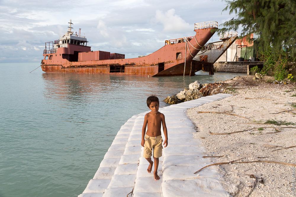 Кирибатийский мальчик идёт по берегу лагуны на фоне ржавого разбитого корабля. Атолл Тарава, Кирибати, Микронезия. A local Kiribati boy walks along the shore of the lagoon. А rusty shipwreck in the background. Tarawa atoll, Kiribati, Micronesia.