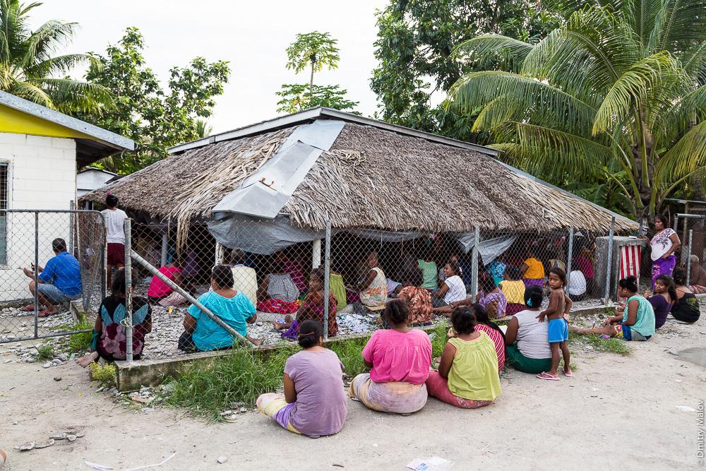Люди собрались в традиционном общественном доме — манеаба. People gathering in a maneaba (traditional meeting house). Атолл Тарава, Кирибати, Микронезия. Tarawa atoll, Kiribati, Micronesia.