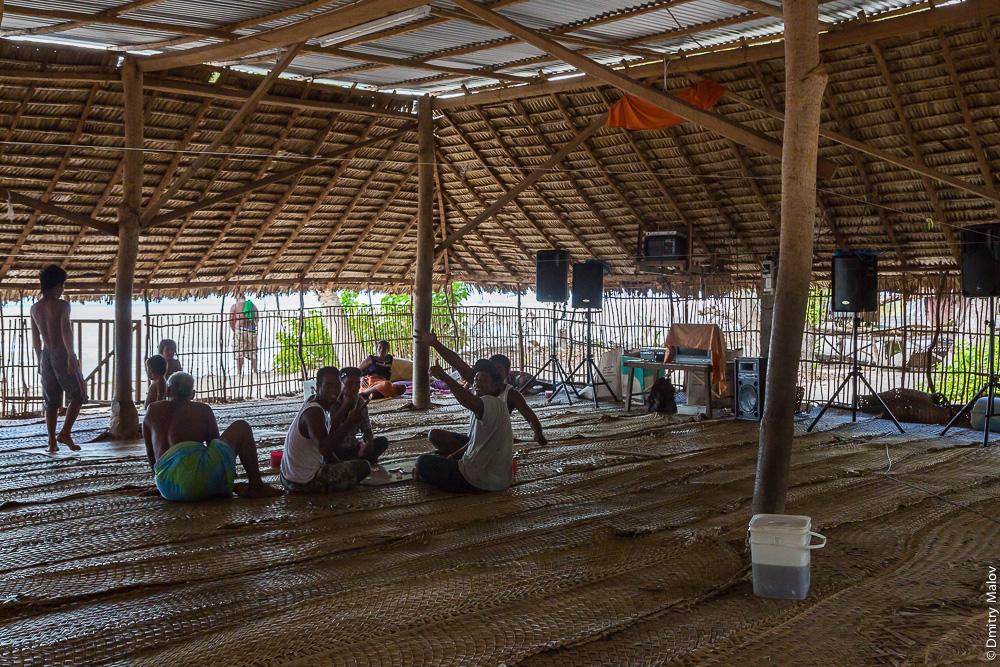 Люди сидят внутри в традиционном общественном доме — манеаба. Музыкальный центр, колонки. People gathering sitting inside a maneaba (traditional meeting house). Music center and speakers. Атолл Тарава, Кирибати, Микронезия. Tarawa atoll, Kiribati, Micronesia.