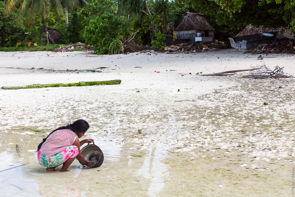 Местная женщина моет в отлив в лагуне посуду (котёл) на фоне мусора. Атолл Тарава, Кирибати, Микронезия. А local woman washes a cauldron in the low tide in the lagoon, garbage around. Tarawa atoll, Kiribati, Micronesia.