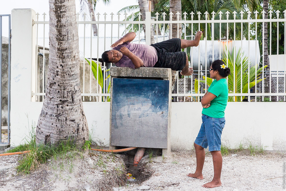 Микронезиец лежит на электрическом/телефонном шкафу, на него смотрит местная жительница. Атолл Тарава, Кирибати, Микронезия. Micronesian man rests, a local woman looks at him. Tarawa Atoll, Kiribati, Micronesia