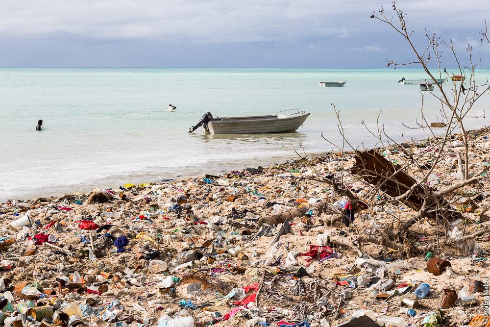 Двое рыбаков с лодкой ловят рыбу в лагуне у сильно замусоренного берега. Атолл Тарава, Кирибати, Микронезия. Two fishermen with a boat fishing in the lagoon at heavy littered shore. Tarawa atoll, Kiribati, Micronesia.