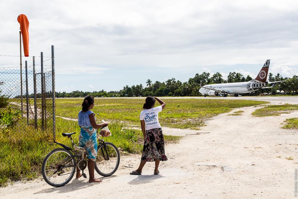 Взлётно-посадочная полоса аэропорта Кирибати, Тарава. Две микронезийские девочки-подростка наблюдают за взлётом самолёта. Kiribati airport runway, Tarawa, departure of Fiji Airways Boeing 737-800 (DQ-FJM). Two local teenage girls with a bicycle looking at a departing airplane