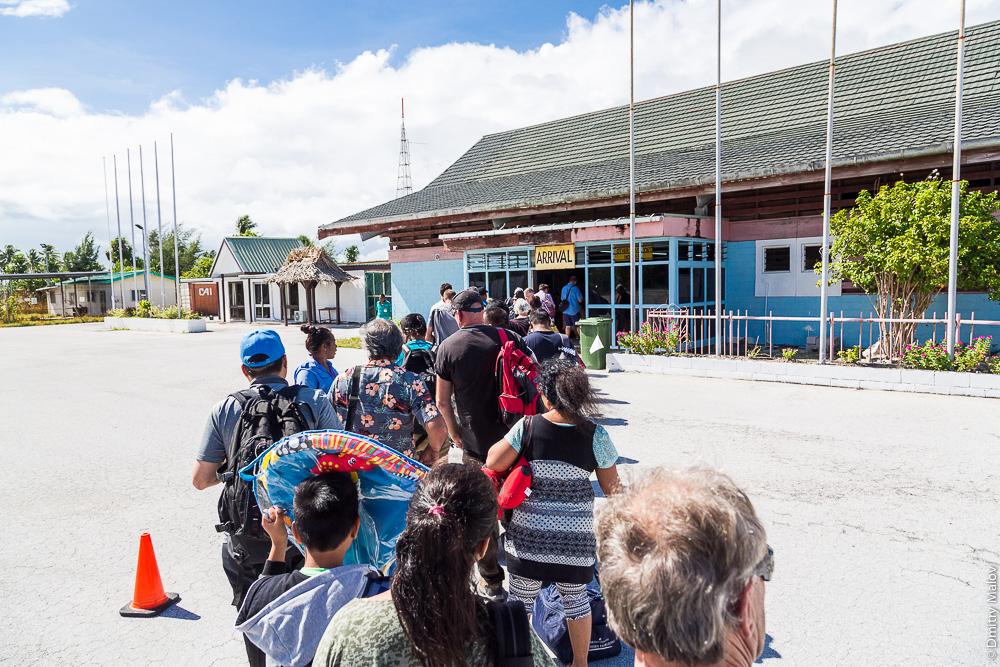 Прибытие в международный аэропорт Кирибати на атолле Тарава. Пассажиры стоят в очереди на перроне. Bonriki International Airport arrival, atoll of Tarawa, Kiribati. Passengers queuing at the airport apron.