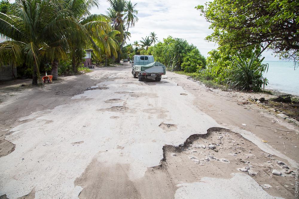 Дорога вокруг атолла Тарава. Ямы, выбоины, колдобины. The main road around Tarawa atoll with huge potholes. Южная Тарава, Кирибати, Микронезия. South Tarawa, Kiribati, Micronesia.