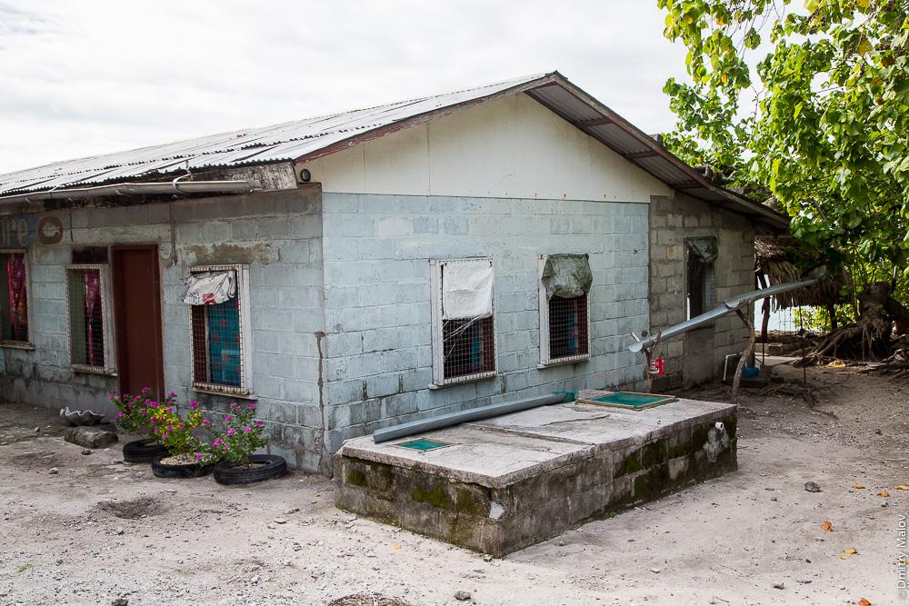Жилой дом из пеноблоков с жестяной крышей. Cобирают дождевою воду с крыш в баки. Южная Тарава, Кирибати, Микронезия. Residential house. Collecting of rain water from the roof to tanks. South Tarawa, Kiribati, Micronesia.