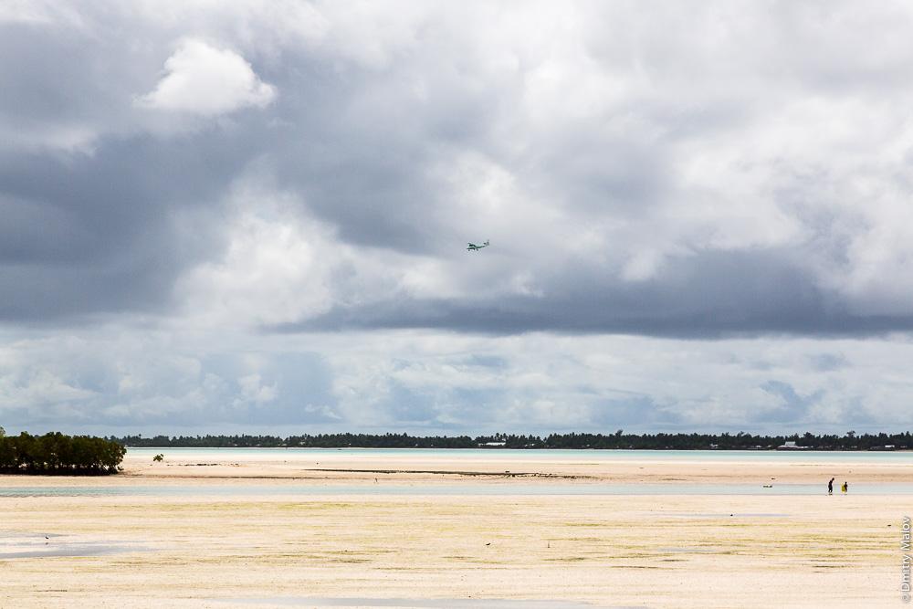 Отлив в лагуне, люди, самолёт в небе. Атолл Тарава, Кирибати, Микронезия. The low tide in the lagoon, people, a plane in the sky. Tarawa atoll, Kiribati, Micronesia.