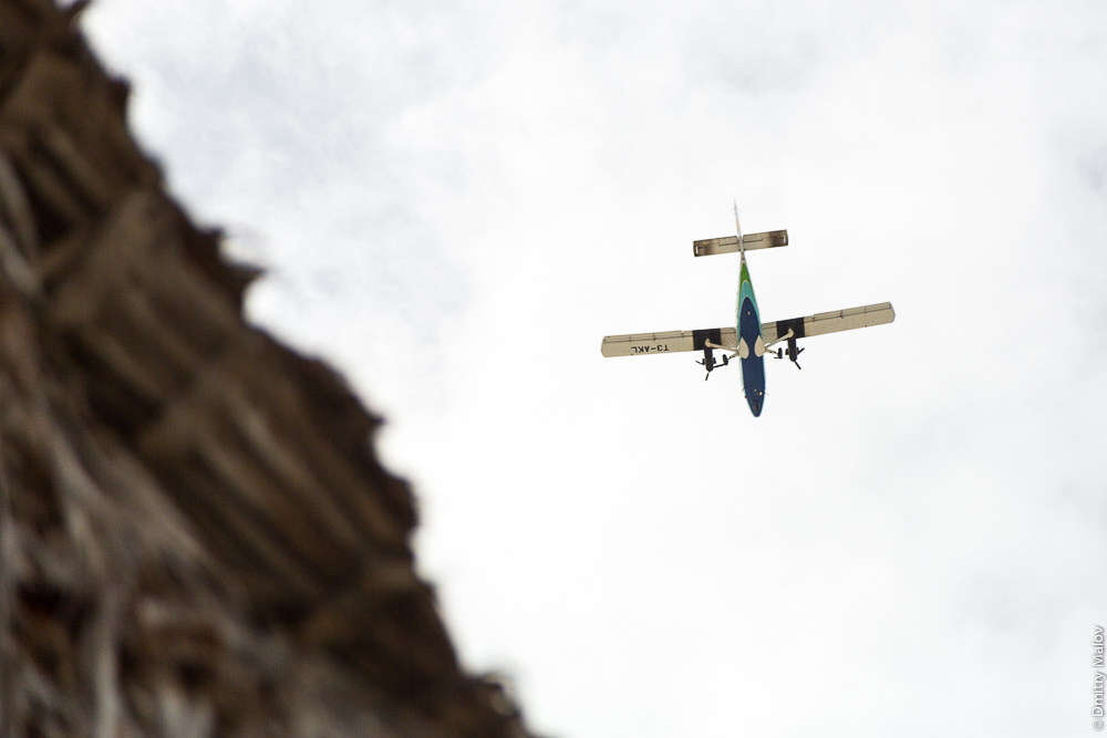 Air Kiribati De Havilland Canada DHC6 Twin Otter T3-AKL in the sky by a pandanus thatched roof