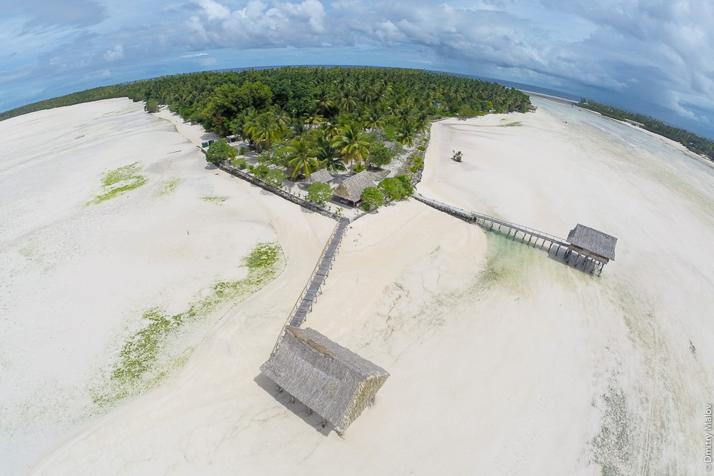 Отлив в лагуне, традиционные дома-хижины из пандануса на сваях с крышами из листьев. Аэрофотосъёмка, фото с дрона. Атолл Тарава, Кирибати, Микронезия. Drone aerial foto of the low tide in lagoon. Traditional pandanus wood thatched roof overwater huts (houses) called buia. Tabon Te Keekee Eco Lodge, North Tarawa, Kiribati, Micronesia.
