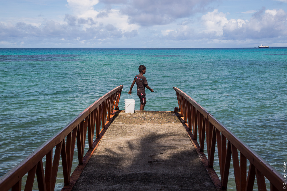 Деревня Ваиаку, атолл Фунафути, Тувалу. Vaiaku village, Tuvalu. A local Polynesian boy fishing at a pier. Местный полинезийский мальчик рыбачит с пирса.