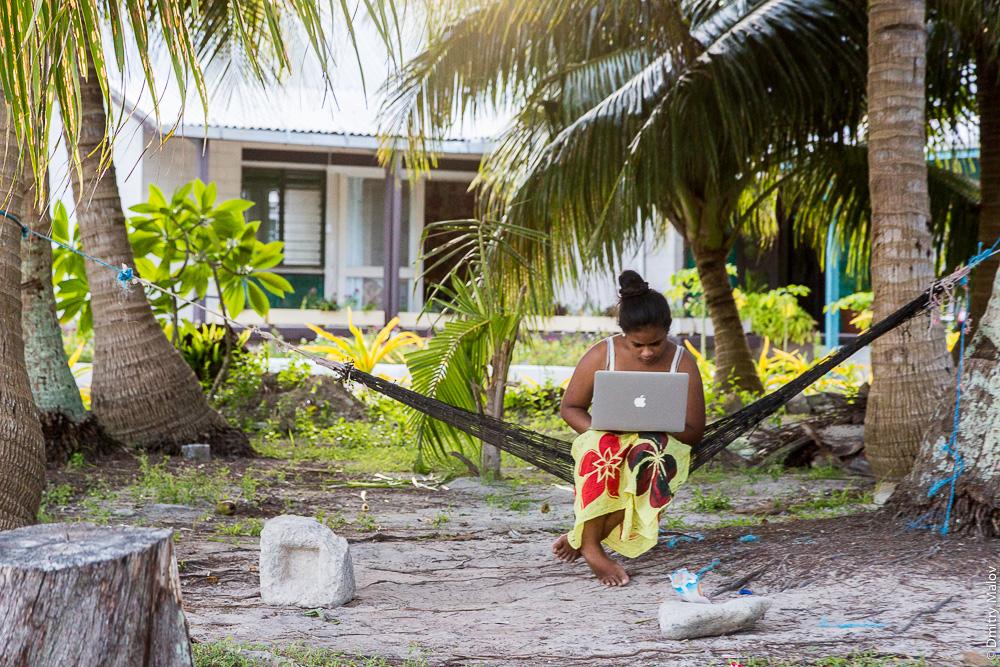 Местная полиннзийская женщина с макбуком сидит в гамаке, Тувалу. A local Polynesian woman with a MacBook is sitting in a hammock, Tuvalu.