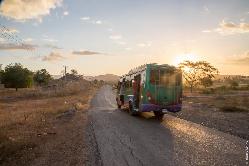 Восточный Тимор, автобус едет по сельской дороге на закате. East Timor, Timor-Leste, sunset and a bus on a countryside