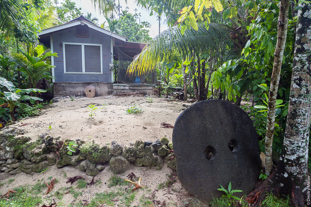 Two huge stone money rai by a porch of a yapese house, Yap Island, Caroline Islands, Federated States of Micronesia. Две гигантские каменные монета раи у крыльца япского дома, Остров Яп, Каролинские острова, Федеративные штаты Микронезии