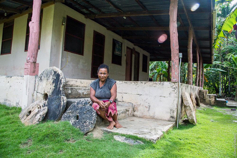 Yapese lady on the porch of yapese house, huge rai stone money nearby, Yap Island, Caroline Islands, Federated States of Micronesia. Местная жительница острова Яп на крыльце своего дома вместе с гигантскими каменными деньгами раи, Каролинские острова, Федеративные штаты Микронезии