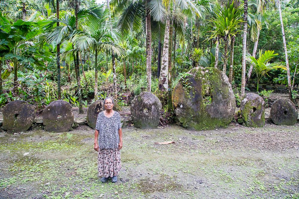Yapese old lady, huge rai stone money bank in jungle on the background, Yap Island, Caroline Islands, Federated States of Micronesia. Пожилая местная жительница острова Яп на фоне банка гигантских каменных денег раи, Каролинские острова, Федеративные штаты Микронезии