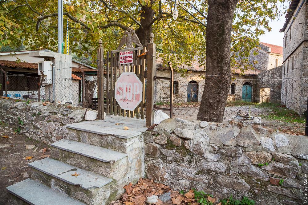 Наземная граница Святой Горы Афон с Грецией, калитка, заграждения и предупреждающие знаки