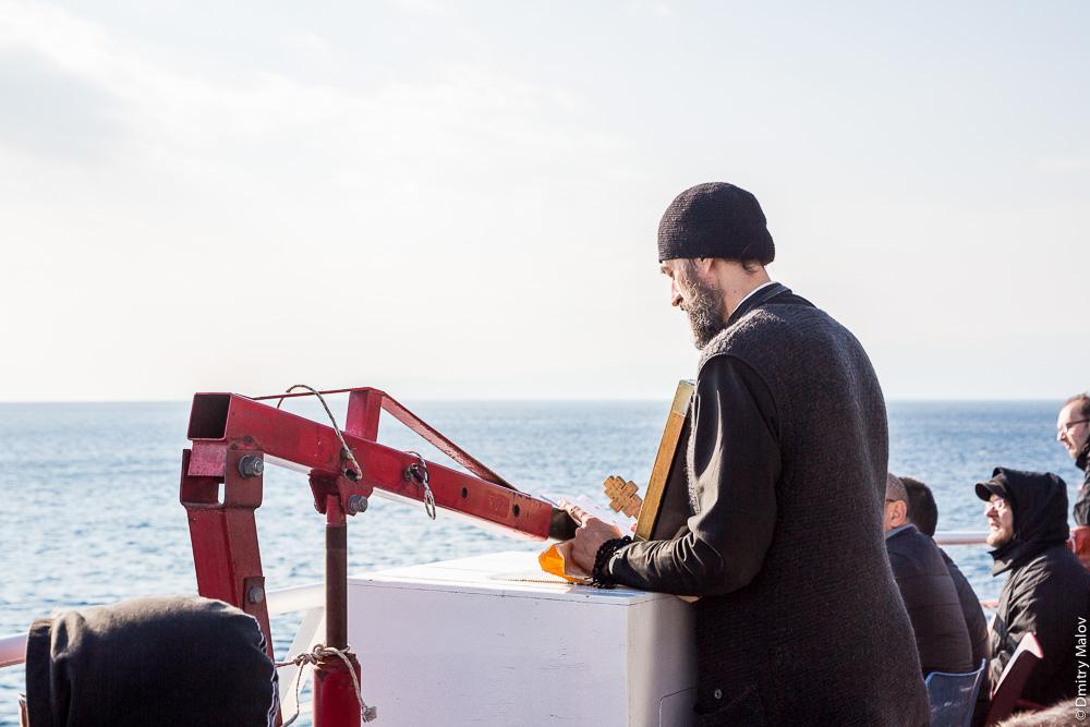 Монах молится на борту парома на Святую Гору Афон. Monk on board the ferry to Mount Athos